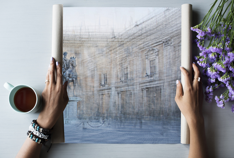 unfolding a print of the image beneath the surface from the homage and the hero collection on a table with tea and flowers