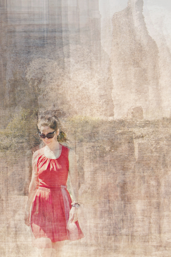 a woman in a ponytail wearing a spring red dress and sunglasses is walking on the palatino hill in rome