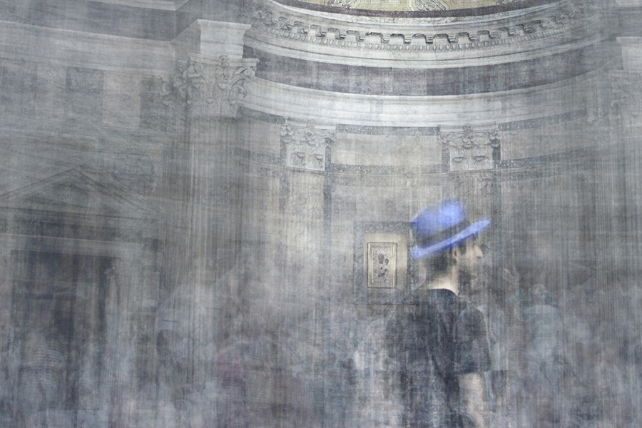 a man wearing a black t-shirt and a blue hat is standing in the middle of the pantheon church in rome