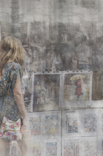 a girl in a summer dress and with a handbag is looking at some posters in piazza navona in rome