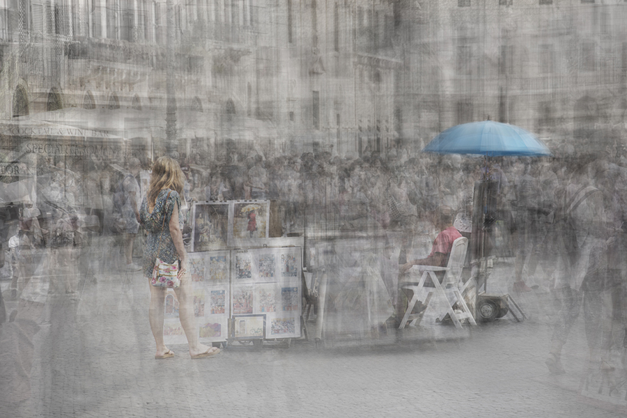 a girl wearing a summer dress and with a handbag is looking at some posters the vendor is seating nearby under an umbrella in piazza navona roma