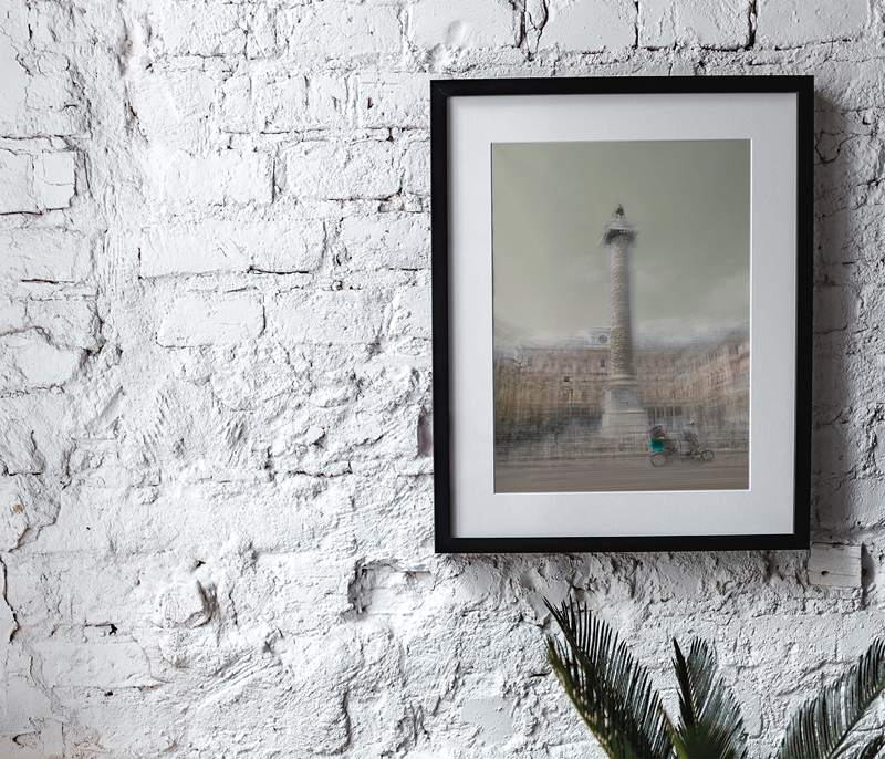 a framed fine art photography print is hanging on a bricked white wall