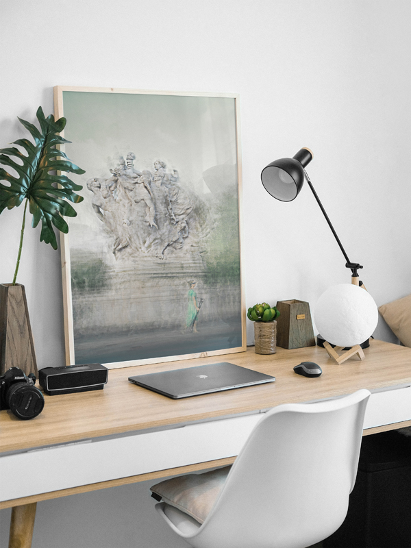 a framed print is on a table next to a lamp and a laptop