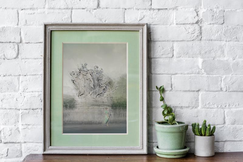 a framed fine art print is on a shelf next to some plants