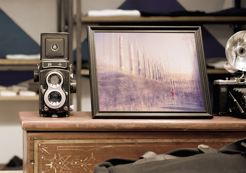 a black frame is on a cabinet next to a camera
