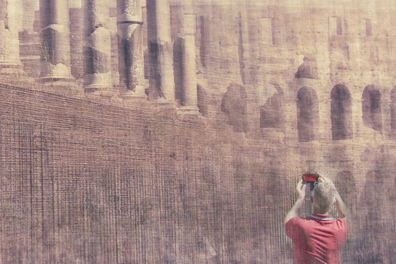 a man wearing a red t-shirt is taking a picture of the colosseum with his smartphone