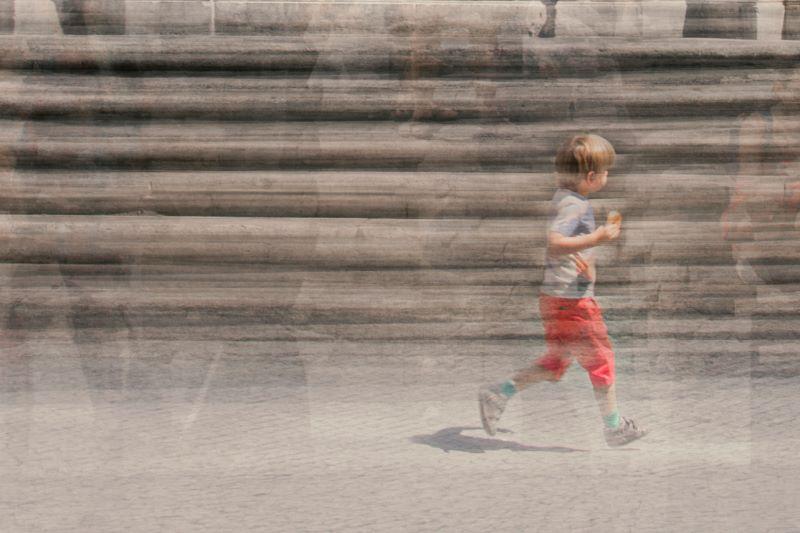 a kid is running in piazza santa maria in trastevere in rome italy