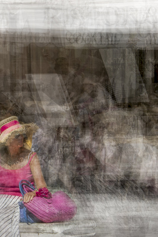 a woman wearing a hat and a pink top is seating on a bench in piazza navona in rome