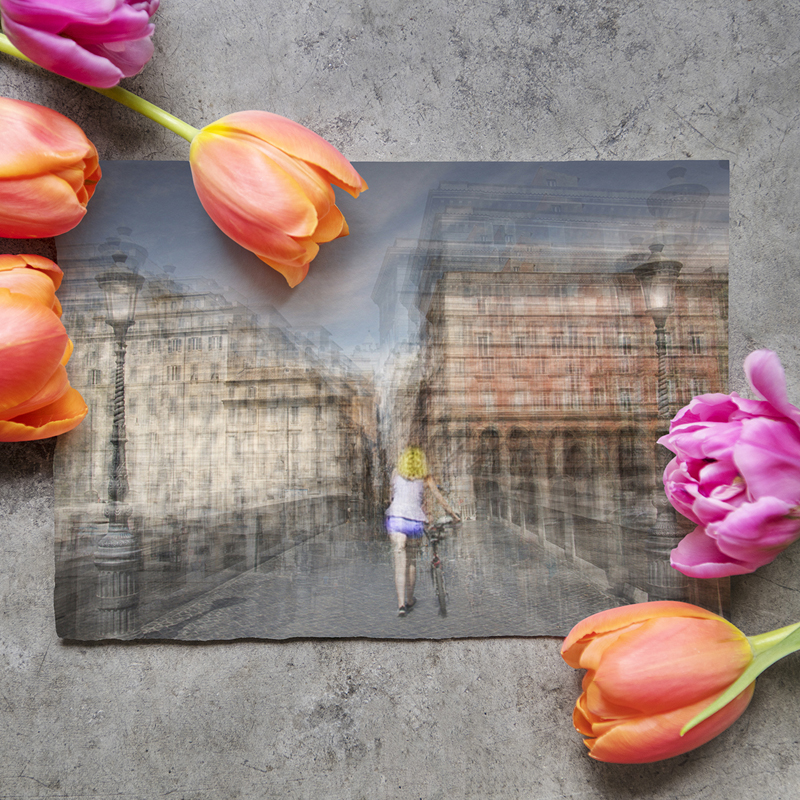 a fine art photography print on a table next to some flowers