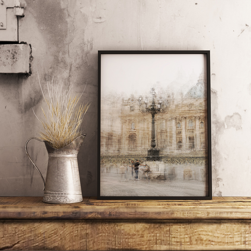 a framed print is on a shelf next to a vase