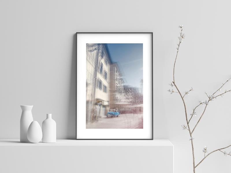 a framed fine art print is next to some white ceramic vases