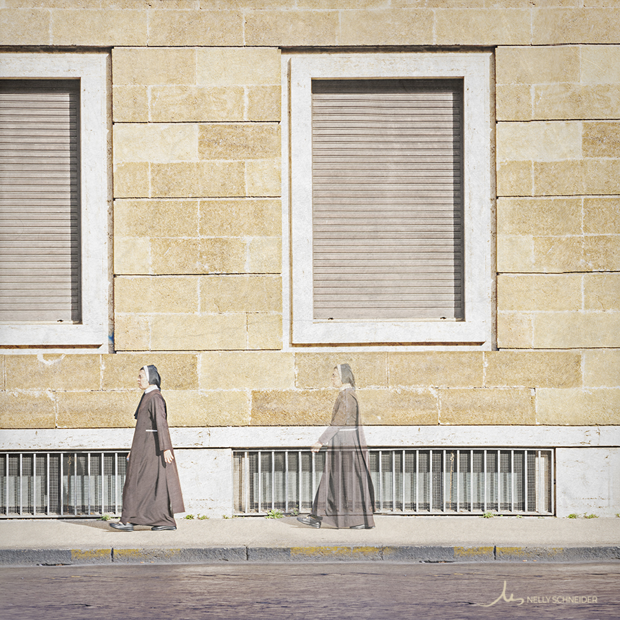 a nun is walking on the sidewalk and and another version of herself follows