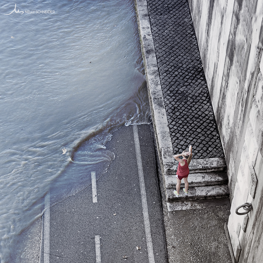 a woman in a red runner outfit is fixing her hair next to the tiber river overflowing the bike lane in rome